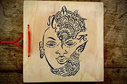 A wooden notebook with an elaborate face and design drawn on the front.